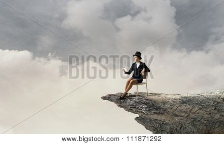 Pretty girl wearing retro hat siting on chair with tablet in hand