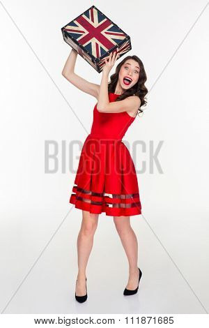 Excited pretty young curly retro styled woman throwing vintage suitcase in camera