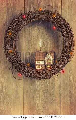 Christmas garland with ceramic cottage and twinkling lights