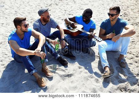 Young men sitting on sand on the riverside