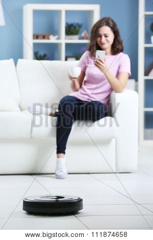 Cleaning concept - automatic robotic hoover clean the room while woman relaxing, close up