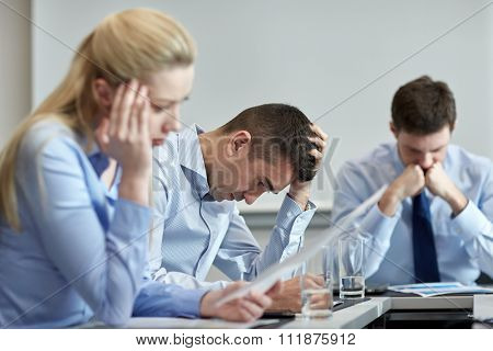business, teamwork, people and crisis concept - business team sitting sad and solving problem in office