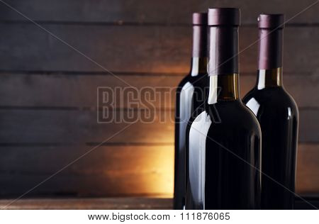 Wine bottles on the table against wooden background