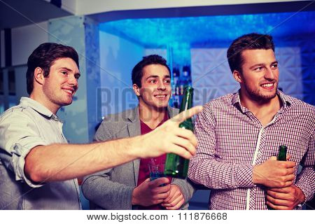 nightlife, party, friendship, leisure and people concept - group of smiling male friends with beer bottles drinking in nightclub