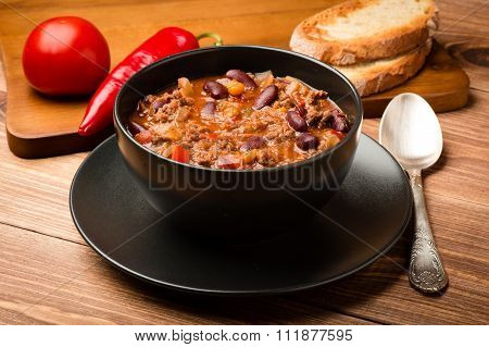 Chili con carne served in the black bowl on the wooden background.