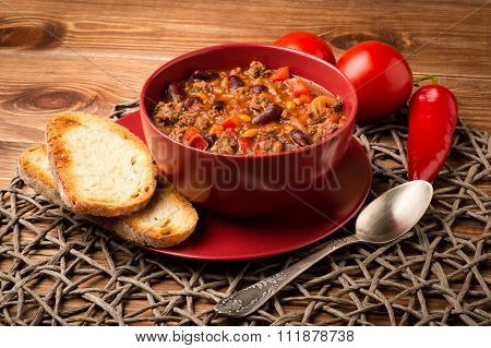 Chili con carne served in the red bowl on the wooden background.