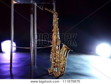 Beautiful golden saxophone near bar stool on a scene
