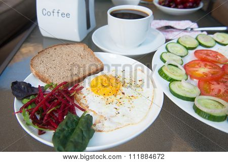 Salad plate and scrambled egg with cup cofee on table