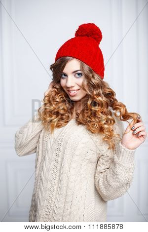 Fashionable Young Girl With Curly Hair In A Red Knitted Hat And Vintage Sweater.