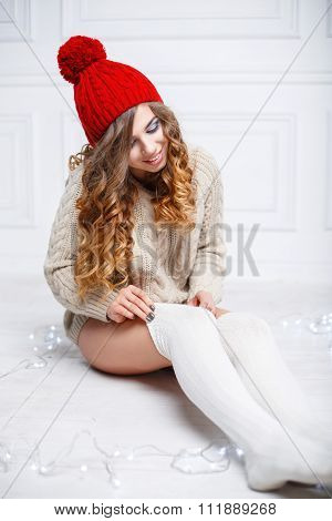 Beautiful Stylish Girl In A Red Warm Hat And Knitted Sweater To Wear Socks.