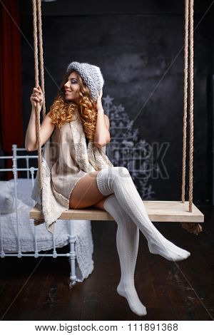 Beautiful Girl In Warm Fashion Clothes On A Swing In The Room