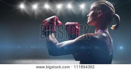 Side view of female boxer with fighting stance against desert landscape