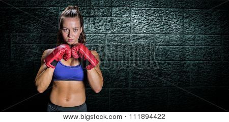 Portrait of pretty woman with fighting stance against grey brick wall