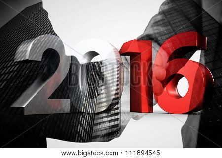 2016 graphic against composite image of business people shaking hands close up