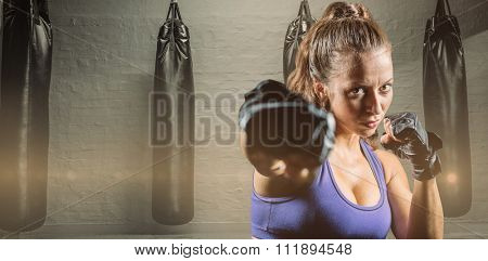 Portrait of female fighter punching against punching bags in red boxing area