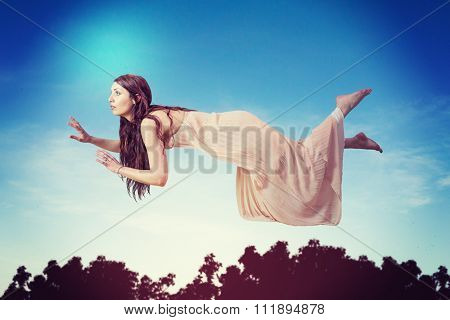 Full length of woman levitating against blue sky with white clouds