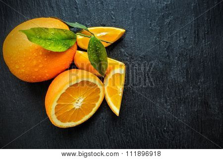 Fresh orange fruit placed on black stone. Shot from aerial view