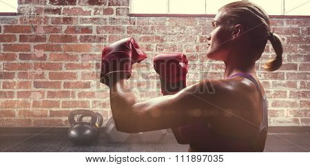 Side view of female boxer with fighting stance against gym