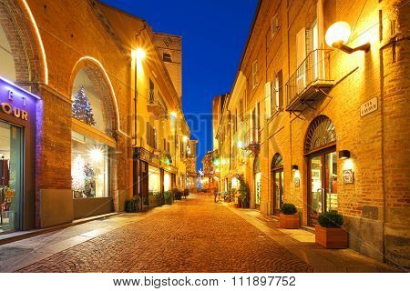 ALBA, ITALY - DECEMBER 07, 2011: Popular tourist street in historic center of Alba with opened shops, bars and stores illuminated and decorated for Christmas and New Year holidays and celebrations.