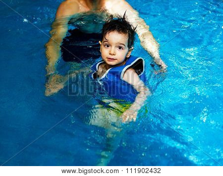 Father holding and  small child. Young boy with inflatable swimming vest in the pool, has a happy sm
