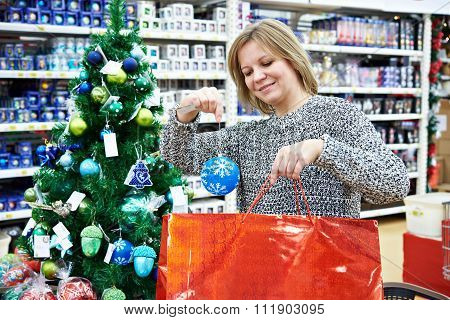 Beautiful Woman Puts A Blue Christmas Ball On A Holiday Red Bag.