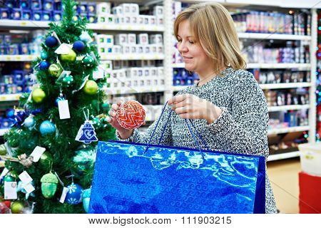 Beautiful Woman Puts A Red Christmas Ball On A Holiday Blue Bag