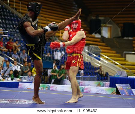 JAKARTA, INDONESIA - NOVEMBER 18, 2015: Dmytro Batok of Ukraine (red) fights Xavier Foupapokam of France (black) in the men's 85kg Sanda event at the 13th World Wushu Championship 2015.