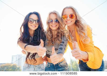 Three happy friends walking in the Park in the summer