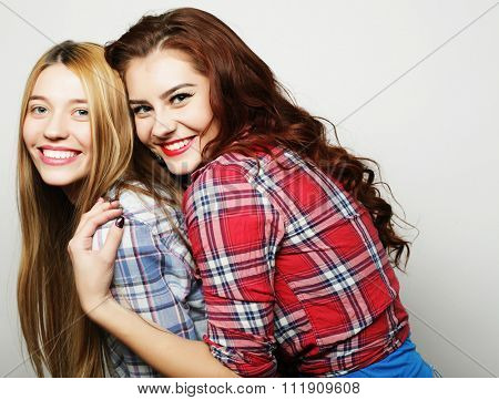 Two young girl friends standing together and having fun. Looking at camera.