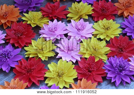 Many Colorful Paper Flowers On A Background With A Smooth Surface