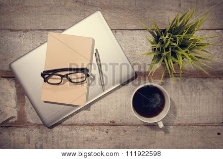 Work desk with laptop computer, diary book, pen, hot coffee cup and eyeglasses. Top view rustic wooden table background in vintage toned.