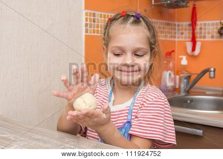 Happy Little Girl Girl Sculpts A Pie At The Kitchen Table