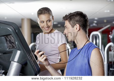 Male Instructor With Young Woman At Gym