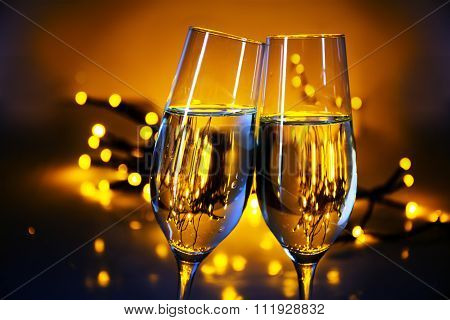 Two Champagne Flutes Clink Glasses At Christmas Or New Year's  Party, Warm Golden Background With Bl