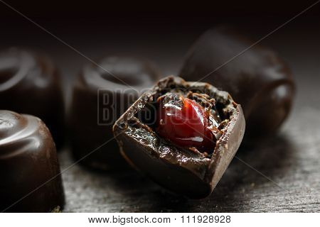 Chocolate Pralines With Red Fruit Filling On A Dark Rustic Wooden Background, Makro Shot