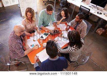 Overhead View Of Designers Having Meeting Around Table