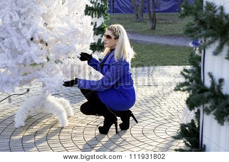 The Beautiful Woman In A Blue Coat Sat Down At A New Year Tree