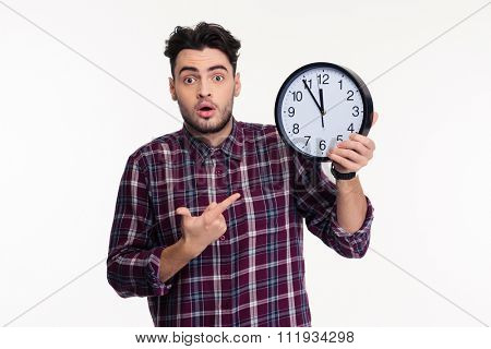 Portrait of a young casual man holding wall clock isolated on a white background