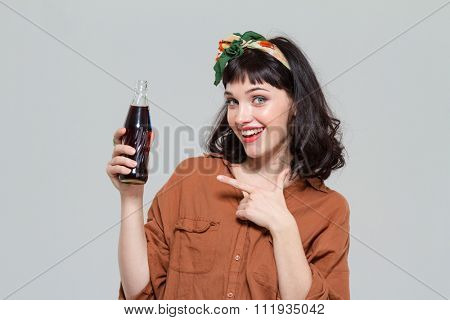 Smiling beautiful young woman pointing on bottle of sweet carbonated beverage isolated over grey background
