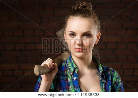 girl in shirt chopping wood with an ax. Brick wall