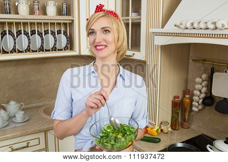 girl looking positive and holding a bowl with salad. It is standing in the kitchen