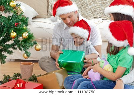 Happy Family Looking At The Little Boy Opening A Christmas Present