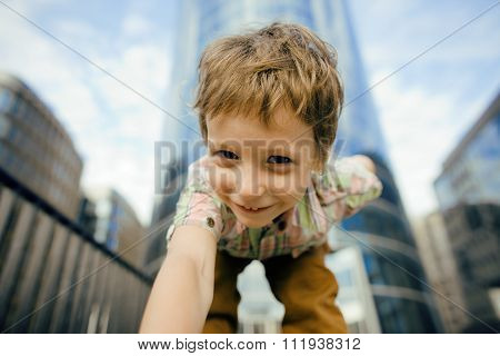 little cute boy standing near business building, smiling close up