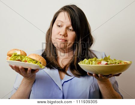 fat white woman having choice between hamburger and salad close up