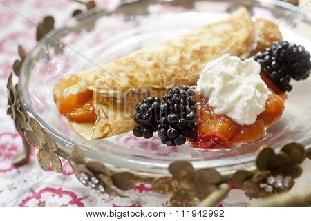 Crepe with whipped cream blackberries and peaches
