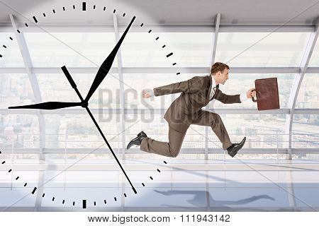 Businessman running with clock background