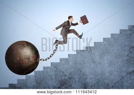Businessman with iron ballast running upstairs