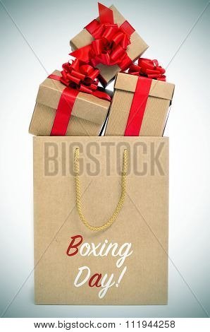 some gifts tied with red ribbon in a paper bag with the text boxing day, with a slight vignette added