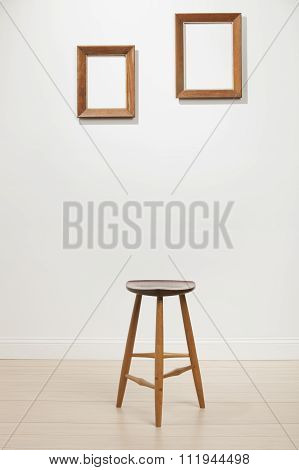 empty frames and chair on a white wall interior