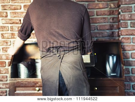 Waiter At Restaurant Processes The Account.